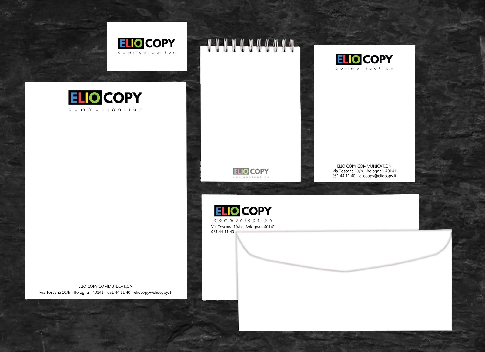 Dark elegance working space with blank notepad, letterhead, business card, coffee cup and earphone on black wood plank background. Template for your design.